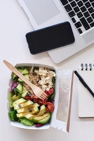 Laptop computer, mobile cell phone and healthy takeout salad, for food delivery takeout application use 스톡 콘텐츠