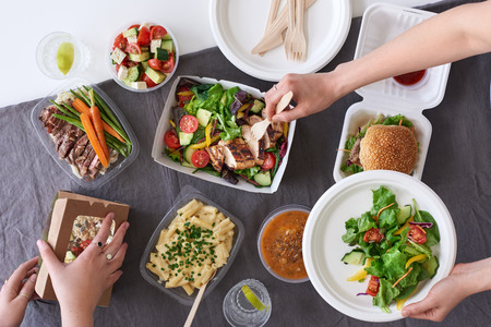 Convenient takeaway takeout food for party, overhead spread of assorted food with hands serving up Stock Photo