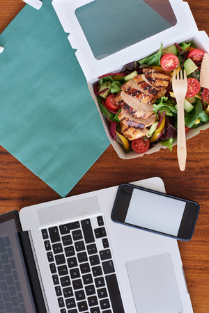 Laptop computer, mobile cell phone and healthy takeaway food, for food delivery takeout application use