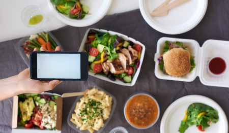Hands holding smartphone mobile cellphone over different types of gourmet takeout, food delivery order app application concept