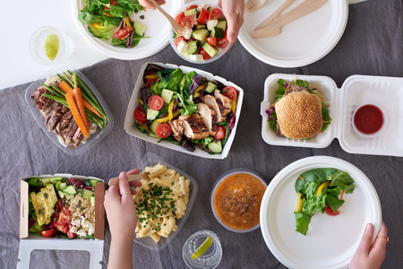 Convenient takeaway takeout food for party, overhead spread of assorted food with hands serving up Standard-Bild