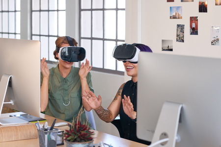 Modern innovative professionals using technology like virtual reality headsets in their work, visualising designed spaces