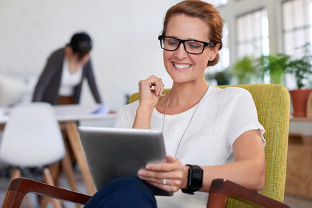 Happy smiling businesswoman looking at portable tablet in creative office photo