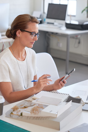 architectural firm: Woman architect interior designer looking at her phone while brainstorming for her latest project