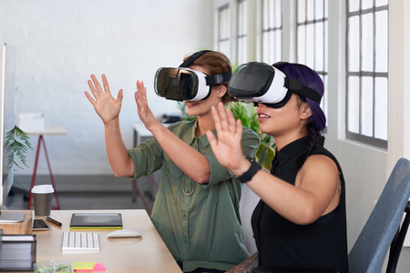 visualise: Asian woman showing her colleague her new project using virtual reality headsets, modern innovative architecture firm Stock Photo