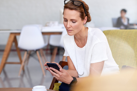 Busy business woman in office reads emails on her smartphone device photo