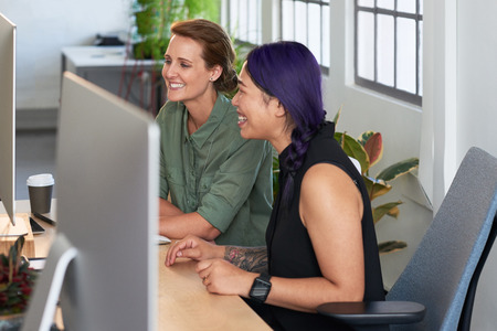 Female coworkers having a discussion at the computer and laughing together, engaging and friendly colleagues photo