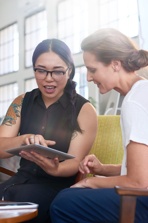 Modern asian business woman with tattoos showing client ideas on portable tablet device photo