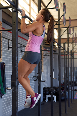 young lady: Fit sporty woman doing bodylifting pull chin up exercises in gym