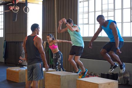 트레이너가 안내하는 나무 상자에 점프하는 크로스 핏 클래스, 체육관에서 강도 훈련 피트니스 운동