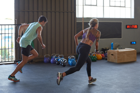 laps: Man and woman race each other to complete laps of sprint sessions in gym during exercise fitness class session