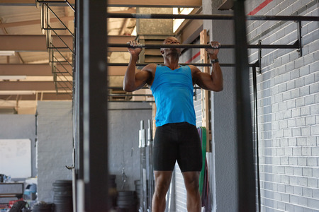 Black african man with large muscles working out in gym with pull-up bar and determination