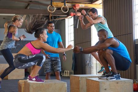 강한 건강한 사람들이 맞는 운동을하면서 격렬한 운동을하는 강사 스톡 콘텐츠