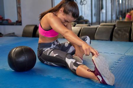 Gym and lifestyle concept, fit healthy woman sitting on floor streching warm up exercise
