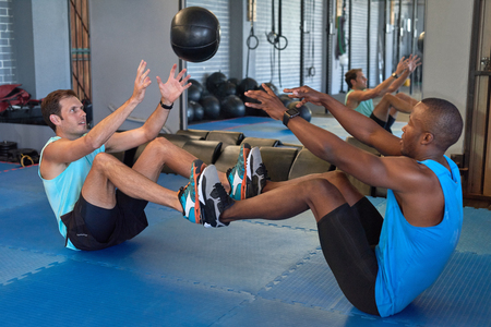 Partner exercises with medicine ball, gym buddies intense training workout