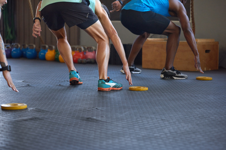 Anonymous people reaching lunging in gym as they run fast short sprints in gym Foto de archivo