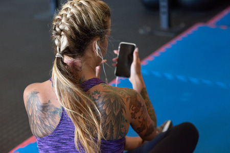 cellular: Anonymous woman in sportswear sporty attire with tattoos using smartphone in gym, fitness exercise app music concept Stock Photo