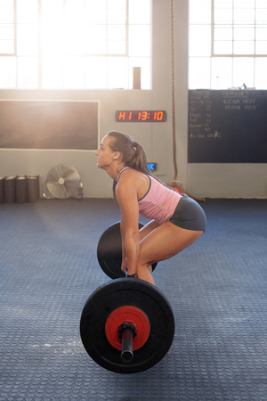 woman with power and good technique lifting weights deadlift in gym Stock Photo