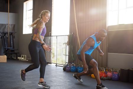 남자와 여자 강렬한 교육 세션 체육관에서 sprinting