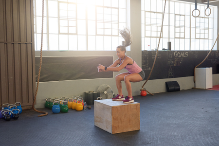 Young fit woman doing box jumps in industrial gym, good form posture technique Stock Photo