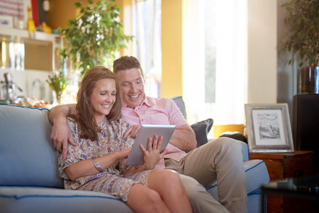 living moment: Young couple looking at tablet pc in cosy home, happy smiling using digital tablet