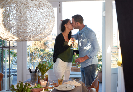 Attractive couple kissing having a moment before their guests arrives for a dinner party