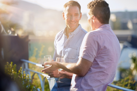 Male buddies talking relaxing having a glass of wine together