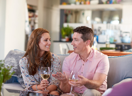 living moment: Real couple talking chatting enjoying glass of wine on the couch in their cosy home