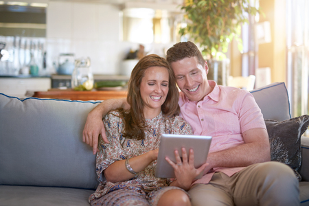 living moment: Young happy couple sitting on couch sofa in living room, watching videos on tablet device Stock Photo