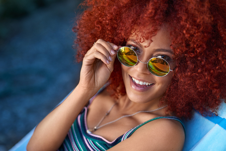 Fun happy portrait of woman with big hair afro and vintage sunglasses outdoors by the pool, carefree happy holiday summer vibes