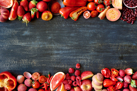 produces: Food frame constructed with red fruits and vegetables, fresh raw organic produce on dark distressed background Stock Photo