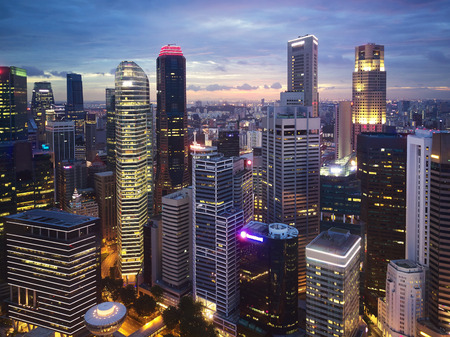 Tall modern skyscrapers business district at twilight lit up, financial centre hub capital urban landscape 版權商用圖片