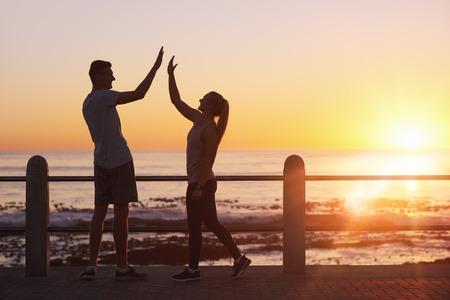 Amigos cinco altos celebrando el final de su carrera a lo largo del océano al atardecer, resplandor naranja brillo del sol en el horizonte