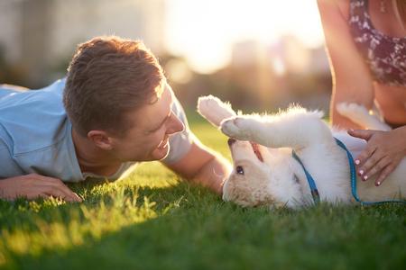 Man spelen met puppy op gras met vriendin, huisdier bonding beste vriend gezonde outdoor levensstijl Stockfoto - 80991731