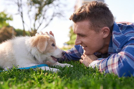 moment: Pet owner bonding with puppy in park on grass, playing petting affection love best friends commitment relationship