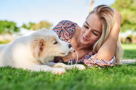 ペットと飼い主の瞬間を愛する公園で子犬と笑顔の女性 写真素材