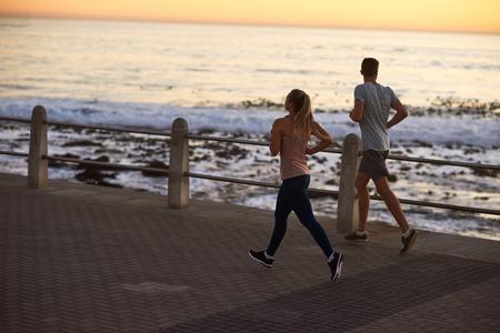 日の出、健康的なアウトドア ライフ スタイルを海に沿って実行しているフィットのアクティブな友人