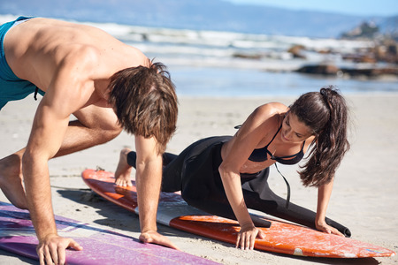 surf instructor demonstrating how to stand up on surfboard in private surf class Foto de archivo