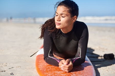 Woman surfer in wetsuit lying on her surfboard enjoying the sunshine, relaxing between surf sessions Stock Photo