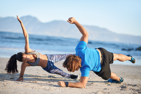 Fit couple doing intense workout on beach side planks strength training, healthy lifestyle