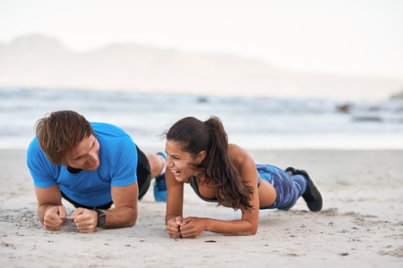 Fitness couple friends talking and laughing while planking on sand, having fun exercising Stock Photo