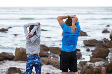 FIt healthy couple stretching their muscles facing the sea, active outdoors lifestyle 版權商用圖片