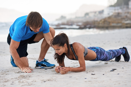 Strong athletic woman planking on beach while personal trainer coach motivates and corrects her posture form