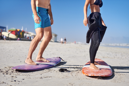 anonymous couple learning how to surf, legs  standing up on surfboards on the beach Reklamní fotografie