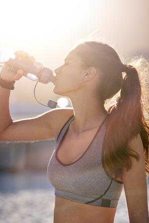 Fit lean athletic woman in sportswear drinks water from bottle, golden sun flare behind