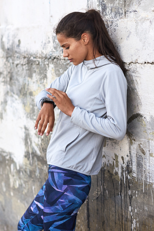 FIt sporty woman looks at exercise tracking app on her smartwatch against grungy wall Stock Photo
