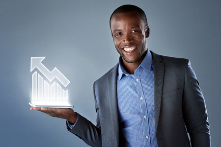 Smiling african businessman in suit showing virtual holographic display of up trend bull market Stock Photo