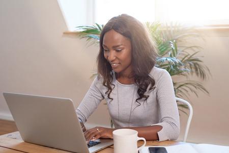 독립적 인 자신감 여자 컴퓨터 노트북에 입력하는 가정에서 일하는 젊은 기업가