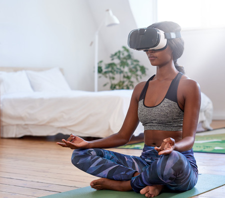 black african woman at home relaxing in meditative pose, virtual reality headset goggles transporting her to nature