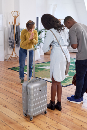 introductions: Asian woman welcomes black couple into her house home accommodation for their holiday vacation trip